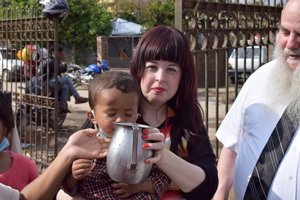 Chani Lifshitz egy nepáli kisfiút itat