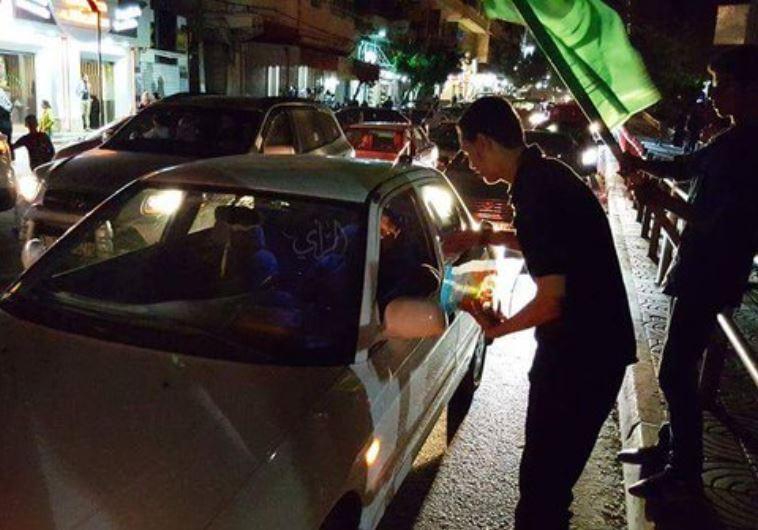 Fiatal arab fiú cukorkát osztgat Tulkaremben egy merénylet után