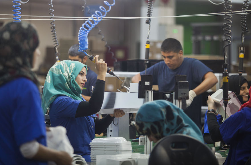 Employees work at the new SodaStream factory built deep in Israel's Negev Desert next to the city of Rahat, Israel, that will replace the West Bank facility when it shuts down in two weeks time, Wednesday, Sept. 2, 2015.  The chief executive of SodaStream, Daniel Birnbaum announced the shuttering of its West Bank factory in the face of international boycott calls, accusing company critics of anti-Semitism, but the Boycott, Divestment and Sanctions (BDS) international boycott campaign declared a victory and said its pressure was behind the decision.  (Photo/Dan Balilty)